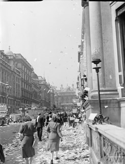 Civilians walk amongst the piles of torn up paper which have been thrown, 'ticker tape'-style, from the windows of offices, on Lower Regent Street, London, to celebrate the signing of the Peace with Japan, 15 August 1945.