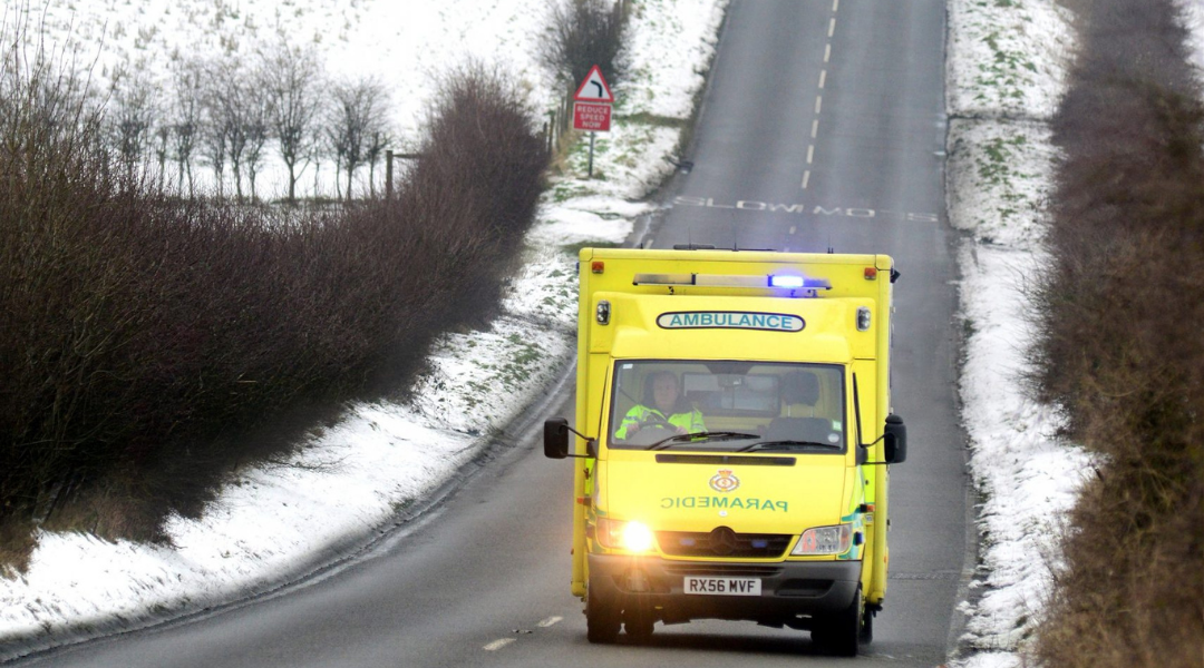A photo of an ambulance driving in winter weather conditions